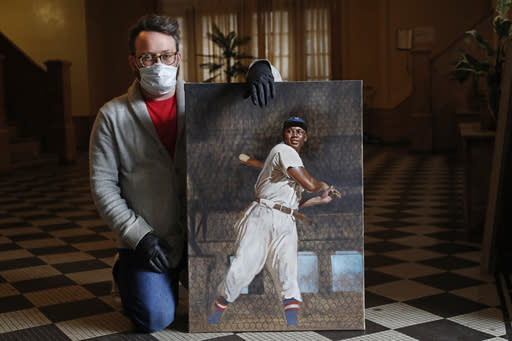 In this Wednesday, April 29, 2020, photo, baseball artist Graig Kreindler poses for a photograph in the lobby of his Brooklyn residence in New York with an unfinished painting of Hall of Famer Josh Gibson showing off his swing. The painting is based on a 1939-40 photograph from Gibson's days with the Cangrejeros (Crabbers) de Santurce, part of the Puerto Rico semi-professional league. That photograph was later used for for Gibson's 1950-51 Toleteros baseball card, now a pricey collectible. During the first half of the 20th century, many African-American players participated in winter ball games in Latin America, earning extra money and escaping racism in the United States. Some 230 of Kreindler's paintings are part of an exhibit celebrating the centennial fo the Negro National League at the National Negro Leagues Baseball Museum in Kansas City, Mo. The museum was forced to temporarily shut down due to concerns over the coronavirus outbreak, but is aiming to reopen in June. (AP Photo/Ka