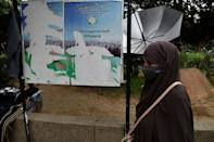 An Algerian woman walks past ripped posters calling on people to vote in a referendum for a new constitution, in the capital Algiers