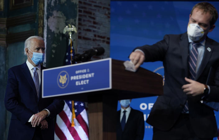 President-elect Joe Biden stands left as the podium is cleaned as he introduces his nominees and appointees to key national security and foreign policy posts at The Queen theater, Tuesday, Nov. 24, 2020, in Wilmington, Del. (AP Photo/Carolyn Kaster)