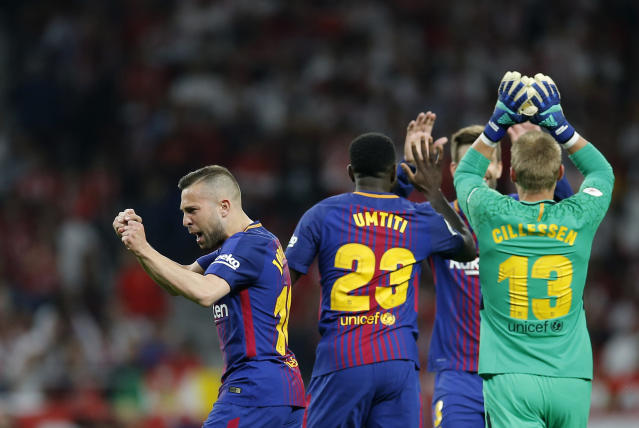 Barcelona's Jordi Alba, left, Samuel Umtiti, center, goalkeeper Jasper Cillessen, right, and Gerard Pique celebrate after Luis Suarez scoring his side's opening goal during the Copa del Rey final soccer match between Barcelona and Sevilla at the Wanda Metropolitano stadium in Madrid, Spain, Saturday, April 21, 2018. (AP Photo/Paul White)