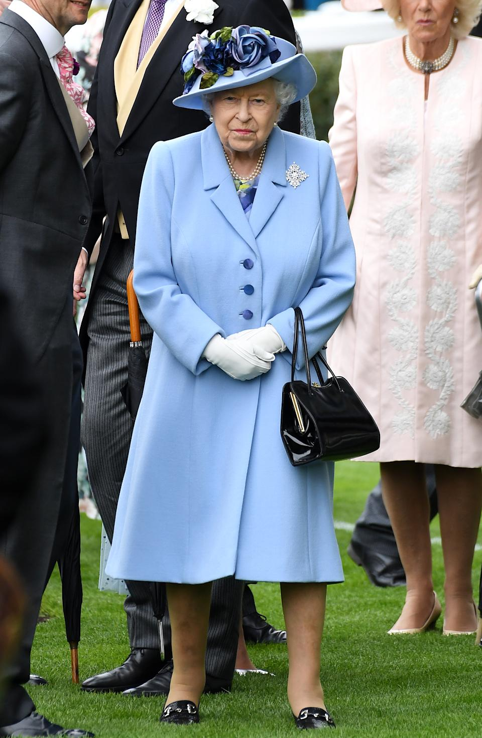 The Queen wore a cornflower blue coat and floral hat, believed to be by Angela Kelly, for day one of Royal Ascot. <em>[Photo: PA]</em>