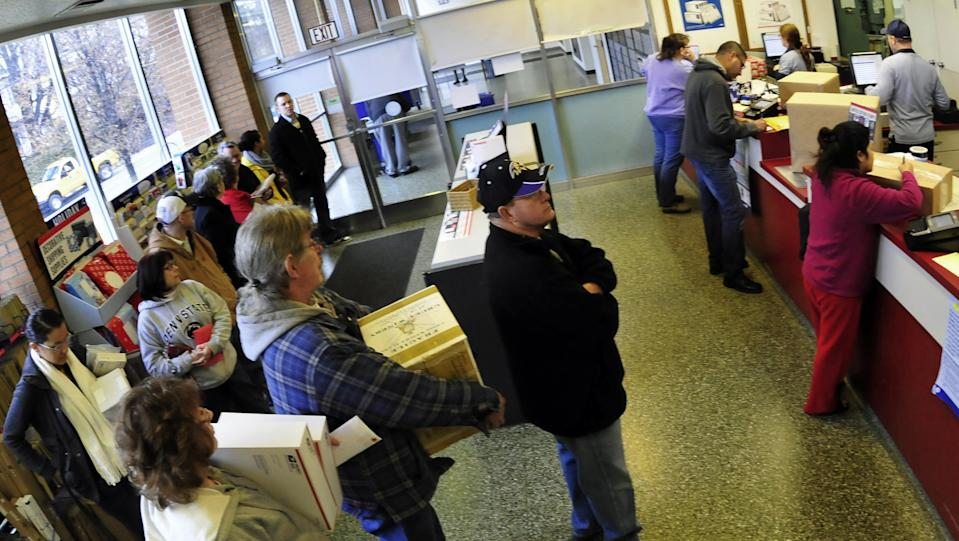 Customers stand in line to mail packages Monday, December 15, 2014, at the U.S Post Office, Chambersburg, Pa. Ten days before Christmas is traditionally the busiest mailing day. (AP Photo/Public Opinion, Markell DeLoatch)