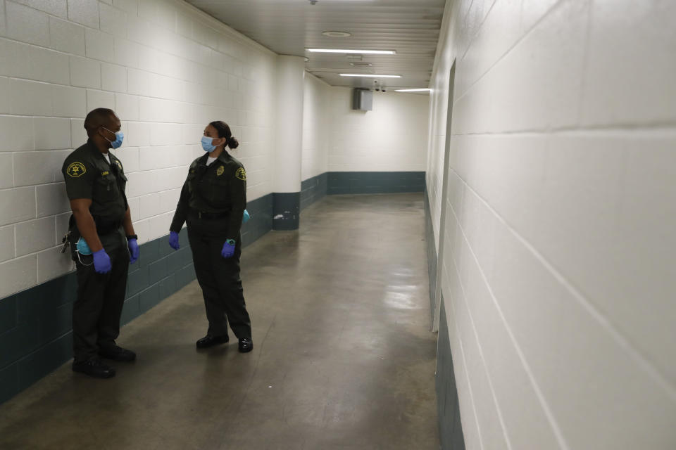 In this April 16, 2020, photo Christopher Lumpkin, left, and Sonia Munoz, custody assistants, talk in the hallway of the hospital ward at the Twin Towers jail in Los Angeles. Across the country first responders who've fallen ill from COVID-19, recovered have begun the harrowing experience of returning to jobs that put them back on the front lines of America's fight against the novel coronavirus. (AP Photo/Chris Carlson)