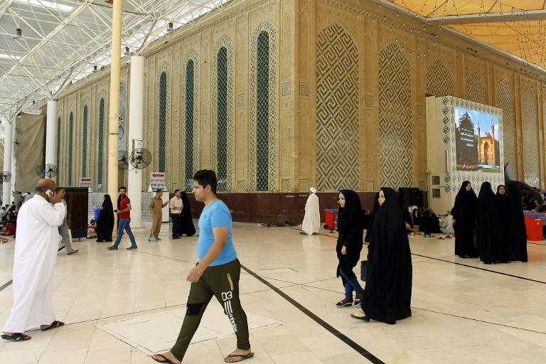 Visitors stroll around a holy site in the Iraqi city of Najaf, a key destination for Iranian Shiite pilgrims, on August 14, 2018