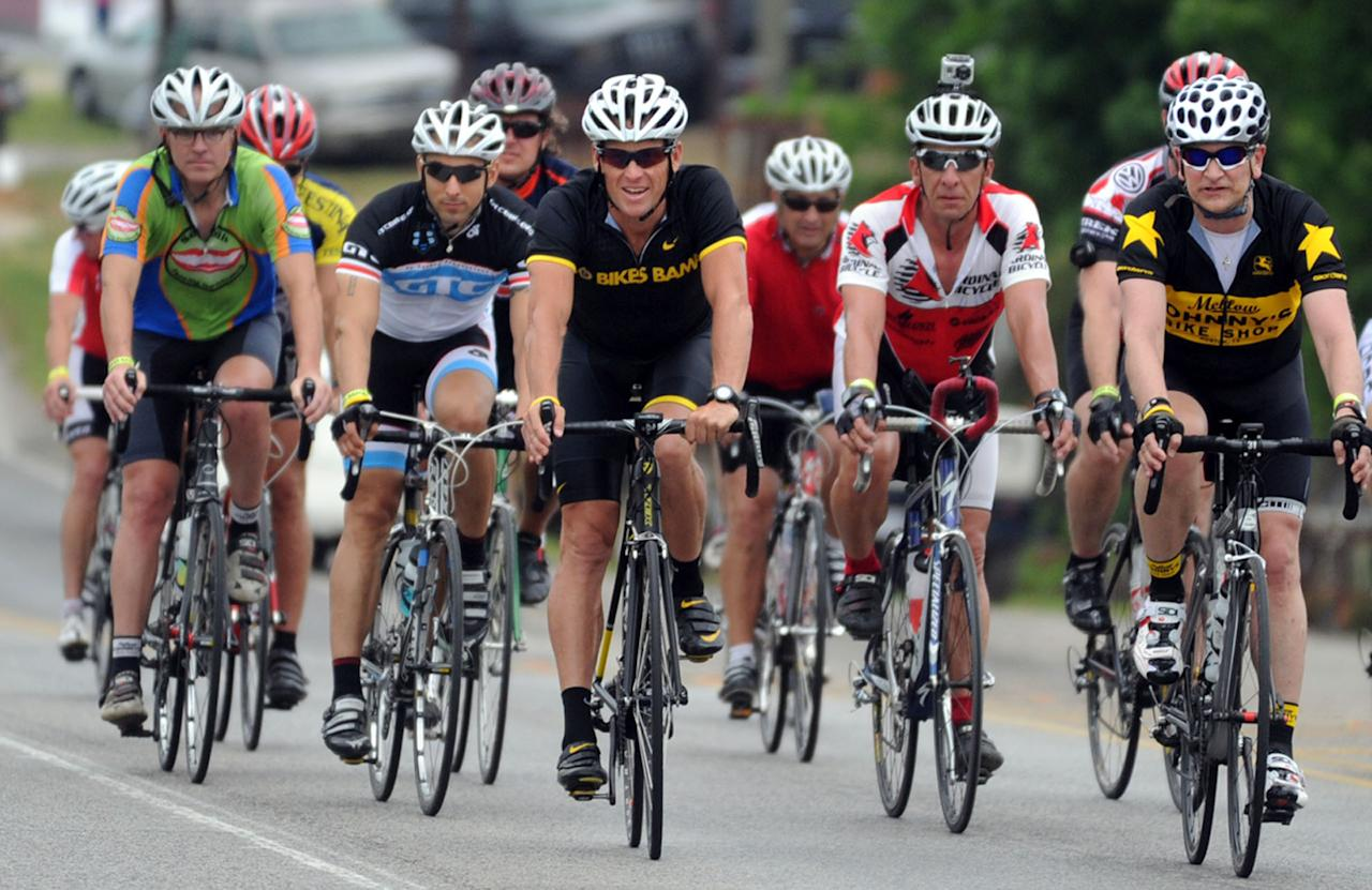 Lance Armstrong (center) leads the pack coming to Jack's restaurant in Pleasant Grove, Ala., Friday, April 27, 2012,, on the fourth day of the Bo Bikes Bama charity bike ride on the one-year anniversary of the deadly Alabama tornadoes. Bo Jackson and about 140 bicyclists and the celebrity bikers rode from Cordova, Ala. to Bessemer, Ala. on Friday. (AP Photo/The News, Linda Stelter) MAGS OUT
