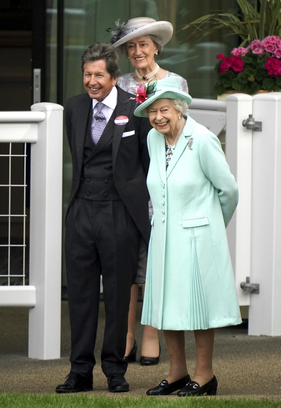 Britain's Queen Elizabeth II, right, stands with racing manager John Warren, during day five of of the Royal Ascot horserace meeting, at Ascot Racecourse, in Ascot, England, Saturday June 19, 2021. (Andrew MatthewsPA via AP)
