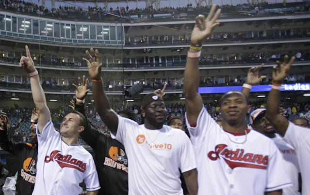 Cleveland Browns quarterback Johnny Manziel, left, and Browns rookies wave to fans before the Cleveland Indians play the Boston Red Sox in a baseball game, Wednesday, June 4, 2014, in Cleveland. (AP Photo/Tony Dejak)