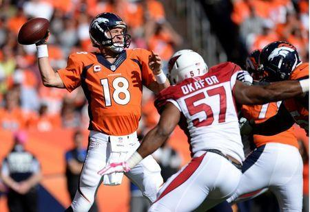 Oct 5, 2014; Denver, CO, USA; Denver Broncos quarterback Peyton Manning (18) looks to pass in the second quarter against the Arizona Cardinals at Sports Authority Field at Mile High. Mandatory Credit: Ron Chenoy-USA TODAY Sports