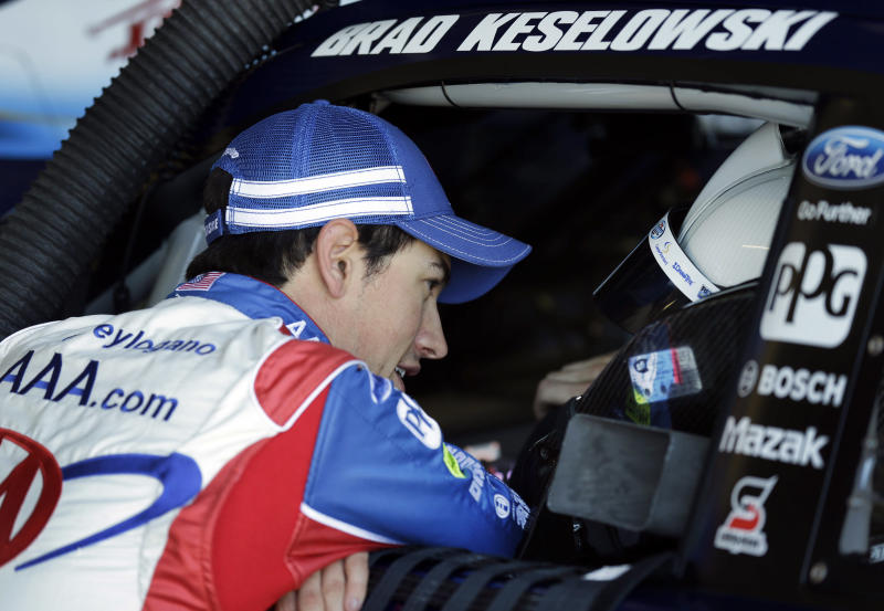 Driver Joey Logano, left, talks with teammate Brad Keselowski during practice for Sunday's NASCAR Sprint Cup series auto race at Kansas Speedway in Kansas City, Kan., Friday, April 19, 2013. (AP Photo/Orlin Wagner)