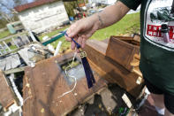 Nicole Beard finds her high school graduation tassel from the class of 1999, as she searches for belongings in the debris of what was the trailer home she lived in, in Hackberry, La., in the aftermath of Hurricane Laura, Saturday, Aug. 29, 2020. (AP Photo/Gerald Herbert)