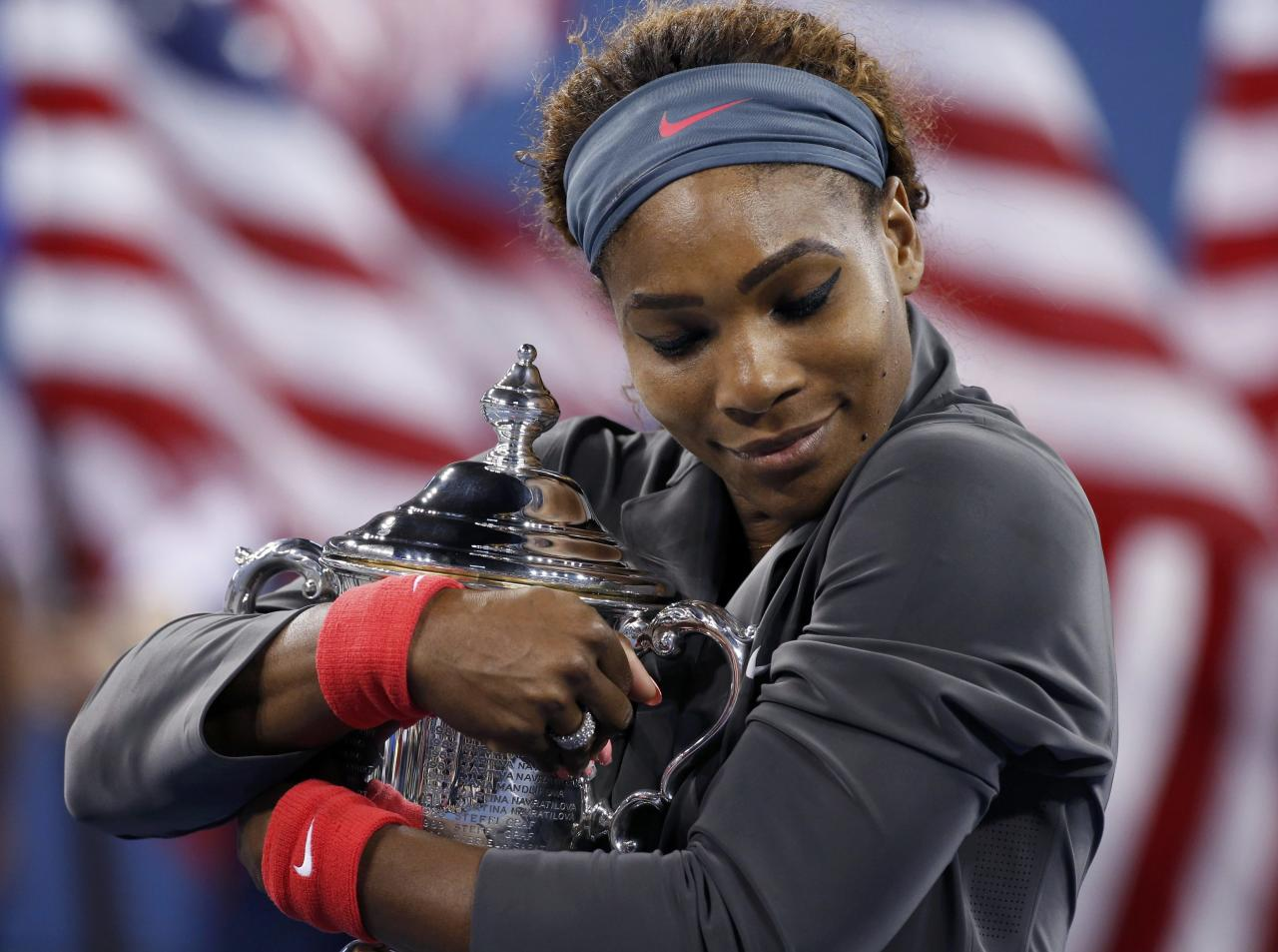 Serena Williams of the U.S. embraces her trophy after defeating Victoria Azarenka of Belarus in their women's singles final match at the U.S. Open tennis championships in New York September 8, 2013. REUTERS/Mike Segar (UNITED STATES - Tags: SPORT TENNIS)