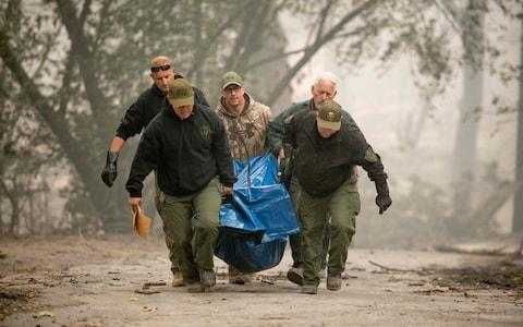 Yuba County Sheriff officers carry a body away from a burned residence in Paradise, California - Credit: AFP