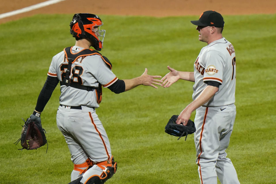 San Francisco Giants pitcher Jake McGee, right, and catcher Buster Posey celebrate after a baseball game against the Philadelphia Phillies, Tuesday, April 20, 2021, in Philadelphia. (AP Photo/Matt Slocum)