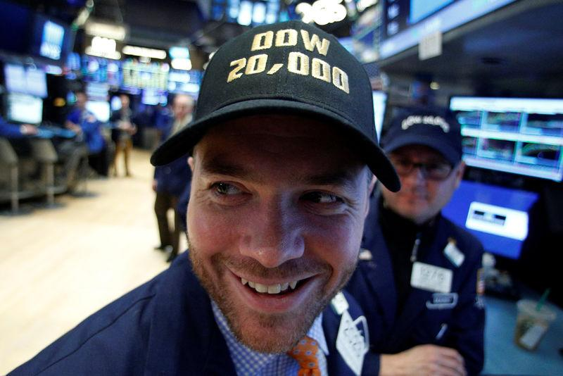 A trader works on the floor of the NYSE as the Dow Jones Industrial Average passes the 20,000 mark in New York