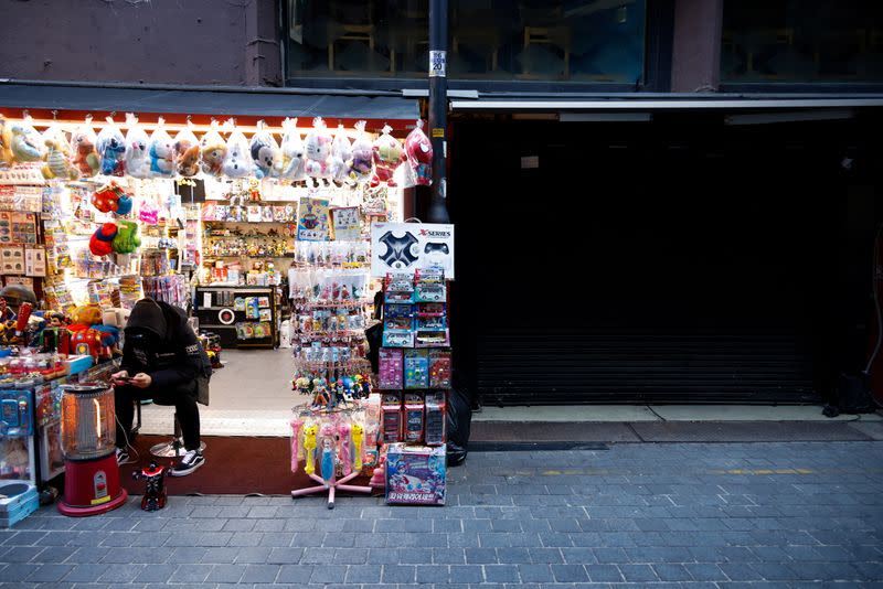 A shopkeeper waits for customers at an empty shopping district amid the coronavirus disease (COVID-19) pandemic in Seoul