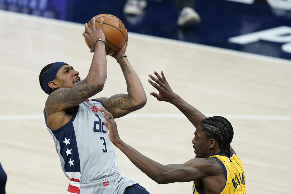 Washington Wizards' Bradley Beal (3) puts up a shot against Indiana Pacers' Justin Holiday (8) during the first half of an NBA basketball game, Saturday, May 8, 2021, in Indianapolis. (AP Photo/Darron Cummings)