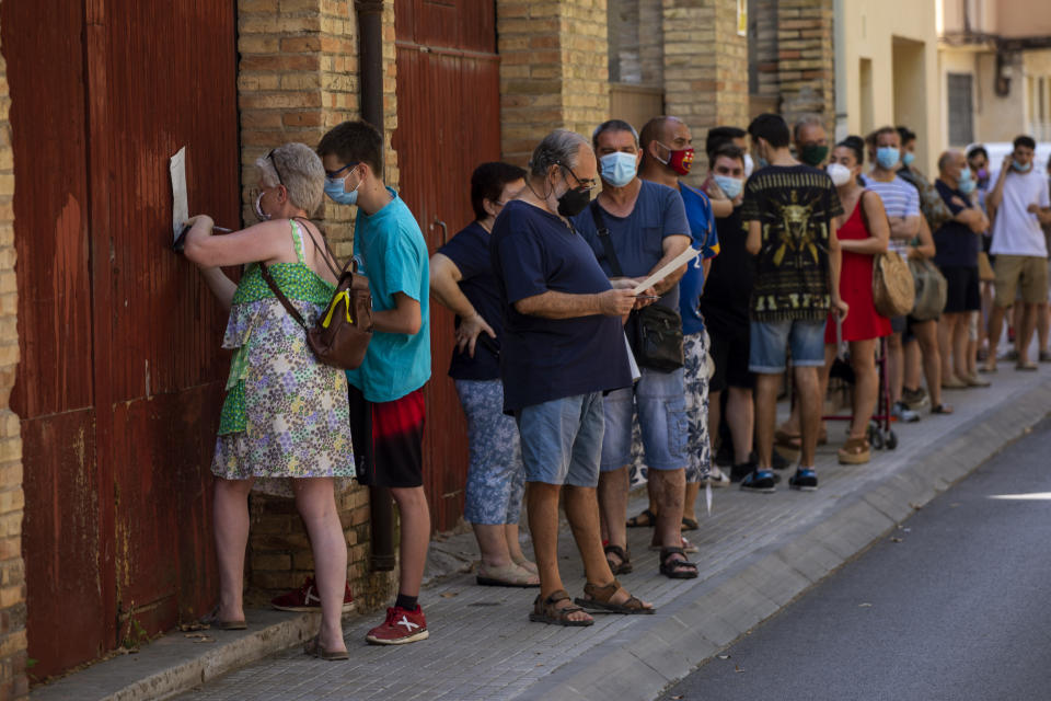 People wearing face masks queue up to be tested for COVID-19, at Vilafranca del Penedes in the Barcelona province, Spain, Monday, Aug. 10, 2020. Spain is facing another surge in coronavirus infections not even two months after beating back the first wave. (AP Photo/Emilio Morenatti)