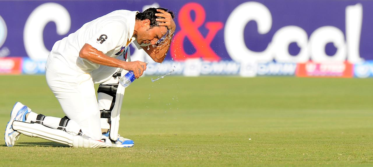 Pakistan batsman Younis Khan takes a water break during the second day of the first cricket Test match between Pakistan and Sri Lanka at the Sheikh Zayed Stadium in Abu Dhabi on January 1, 2014. Sri Lanka were bowled out for 204 in their first innings of the first Test against Pakistan in Abu Dhabi. AFP PHOTO/Ishara S. KODIKARA