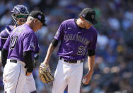 Colorado Rockies manager Bud Black, front left, chats with starting pitcher Kyle Freeland after he was arguing with the home plate umpire as catcher Dom Nunez, back left, looks on in the third inning of a baseball game against the Los Angeles Dodgers, Thursday, Sept. 23, 2021, in Denver. (AP Photo/David Zalubowski)