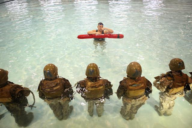 PARRIS ISLAND, SC - FEBRUARY 25: Sgt. Gustavo Ramos of Pomona, California teaches female Marine recruits to remove body armor while under water during boot camp February 25, 2013 at MCRD Parris Island, South Carolina. Male and female recruits are expected to meet the same standards during their swim qualification test. All female enlisted Marines and male Marines who were living east of the Mississippi River when they were recruited attend boot camp at Parris Island. About six percent of enlisted Marines are female. (Photo by Scott Olson/Getty Images)