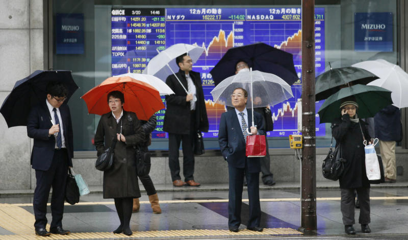 People stand in front of an electronic stock board of a securities firm in Tokyo, Thursday, March 20, 2014. Asian stocks inched down Thursday after comments from the new head of the Federal Reserve suggested U.S. interest rates could rise sooner than financial markets were anticipating. (AP Photo/Koji Sasahara)