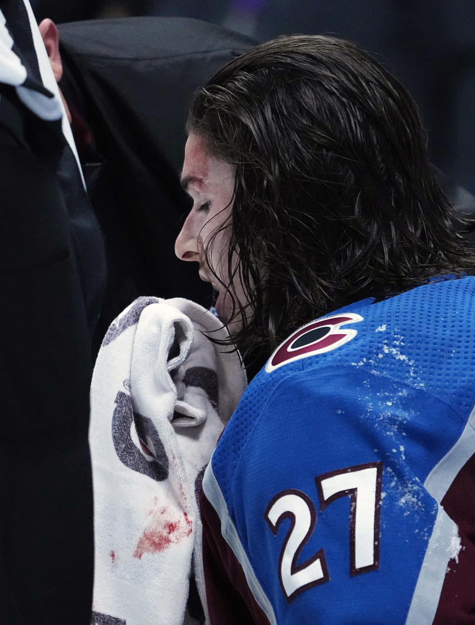 Colorado Avalanche defenseman Ryan Graves (27) wipes blood from his face after a fight against the Vegas Golden Knights in the third period of Game 1 of an NHL hockey Stanley Cup second-round playoff series Sunday, May 30, 2021, in Denver. (AP Photo/Jack Dempsey)