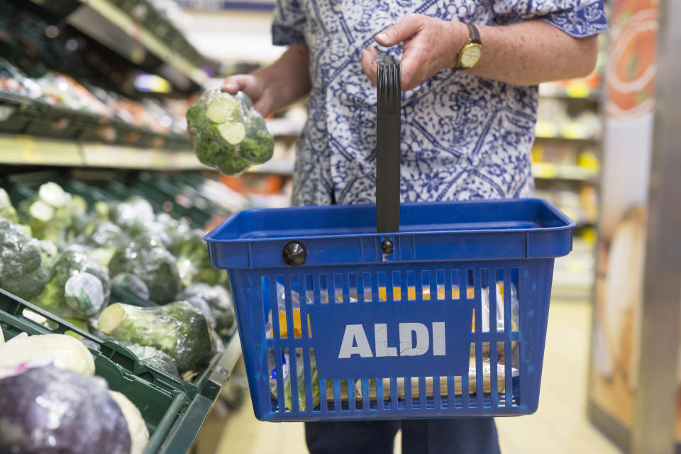 A customer picks a bunch of Broccoli from the vegetable display at Aldi