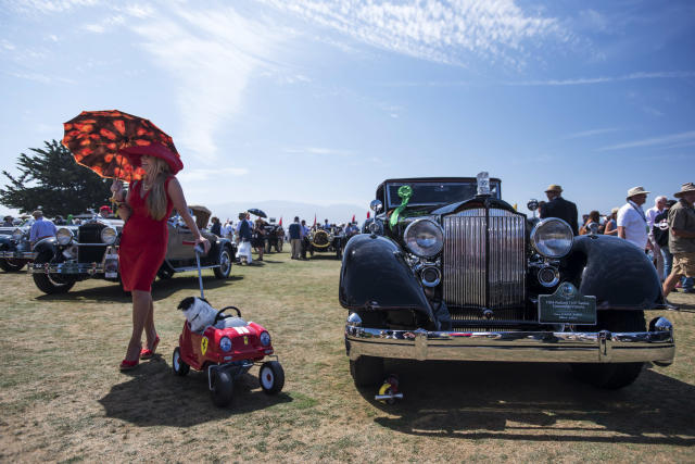 An attendee holding an umbrella and pulling a Ferrari themed cart with a dog poses for a photograph in front of a 1934 Packard 1107 Twelve Convertible Victoria, right, during the Pebble Beach Concours d'Elegance in Pebble Beach, California, U.S. At last year's event sales of vintage cars hit a record $399 million. (David Paul Morris/Bloomberg)