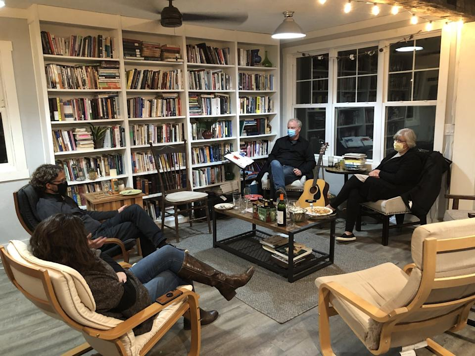 The Rev. Keith Mannes and wife with another pastor and his wife in a room lined with bookshelves.