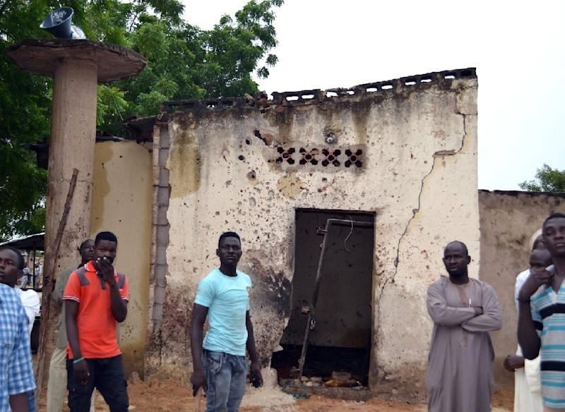 People stand outside a mosque where a suicide bomber killed over 20 worshippers in the city of Maiduguri, northeast Nigeria, on September 21, 2015