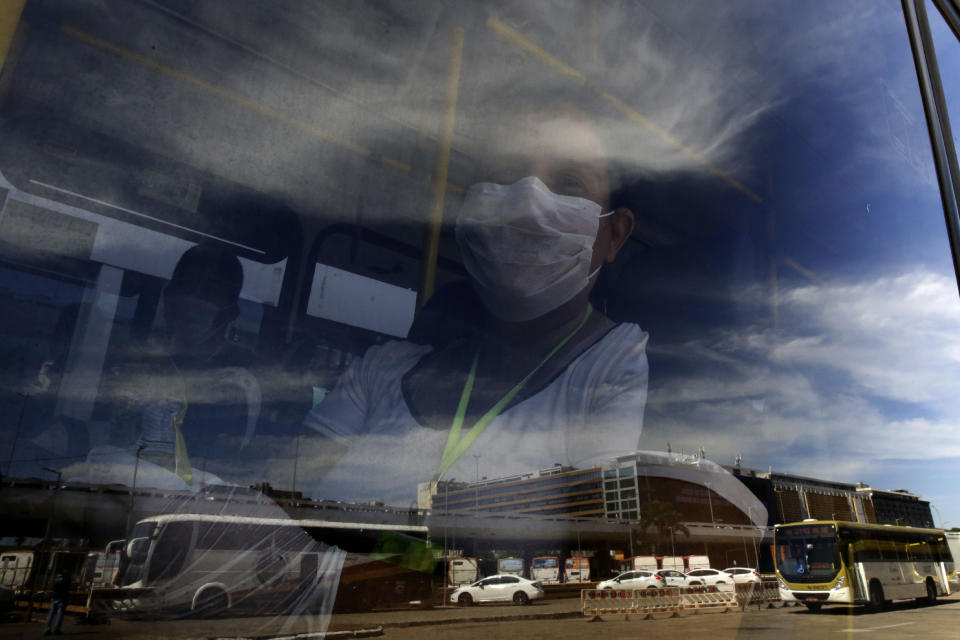 A woman peers from behind a bus window parked at a bus station in Brasilia, Brazil, Monday, May 4, 2020. The state government mandated that commuters using public transportation must wear face masks starting Monday to help contain the spread of the new coronavirus. (AP Photo/Eraldo Peres)