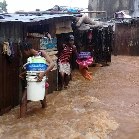 <span>Youngsters flee flooded homes in Regent, near Freetown</span> <span>Credit: Society for Climate Change Communication Sierra Leone/AFP </span>