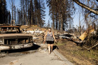 Kimberly Price leaves food for cats at the home of her boyfriend, volunteer firefighter John Hunter, on Sunday, Sept. 5, 2021, in the Greenville community of Plumas County, Calif. Hunter, whose home burned during the Dixie Fire in August, received a motorhome from EmergencyRV.org earlier in the day. (AP Photo/Noah Berger)