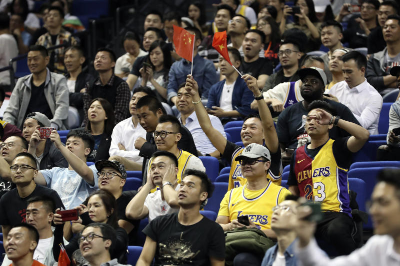 A Chinese fan holds Chinese national flags as he cheers with other fans during a preseason NBA basketball game between the Brooklyn Nets and Los Angeles Lakers at the Mercedes Benz Arena in Shanghai, China, Thursday, Oct. 10, 2019. (AP Photo)