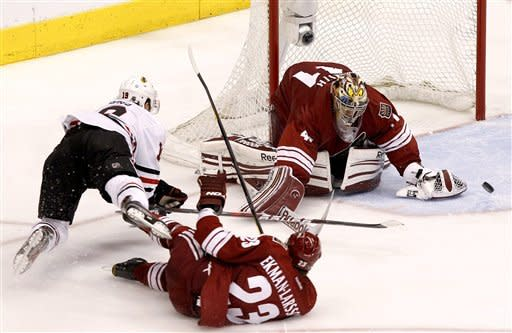 Chicago Blackhawks' Jonathan Toews (19) gets tripped up by Phoenix Coyotes' Oliver Ekman-Larsson (23), of Sweden, as Mike Smith makes a save on the shot during overtime in Game 1 of an NHL hockey Stanley Cup first-round playoff series Thursday, April 12, 2012, in Glendale, Ariz. The Coyotes defeated the Blackhawks 3-2.(AP Photo/Ross D. Franklin)
