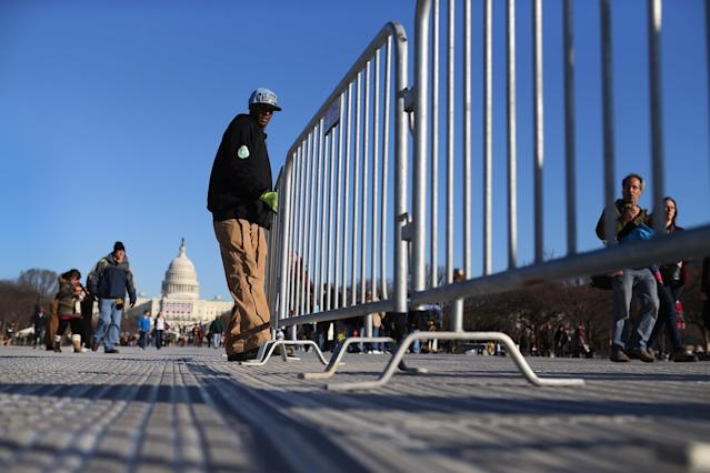WASHINGTON, DC - JANUARY 20: Alvin Martin places barriers in place on the National Mall as preparations continue for the Inauguration ceremony on January 20, 2013 in Washington, DC. The U.S. capital is preparing for the second inauguration of U.S. President Barack Obama, which will take place on January 21. (Photo by Joe Raedle/Getty Images)