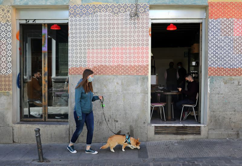 Woman with a dog walks past people inside a bar in central Madrid