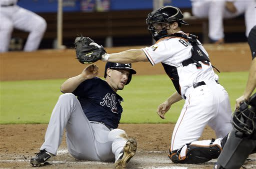 Atlanta Braves' Chris Johnson, left, is out at home after he was tagged out by Miami Marlins catcher Rob Brantly, right, in the fourth inning during a baseball game,Tuesday, July 9, 2013 in Miami. (AP Photo/Lynne Sladky)