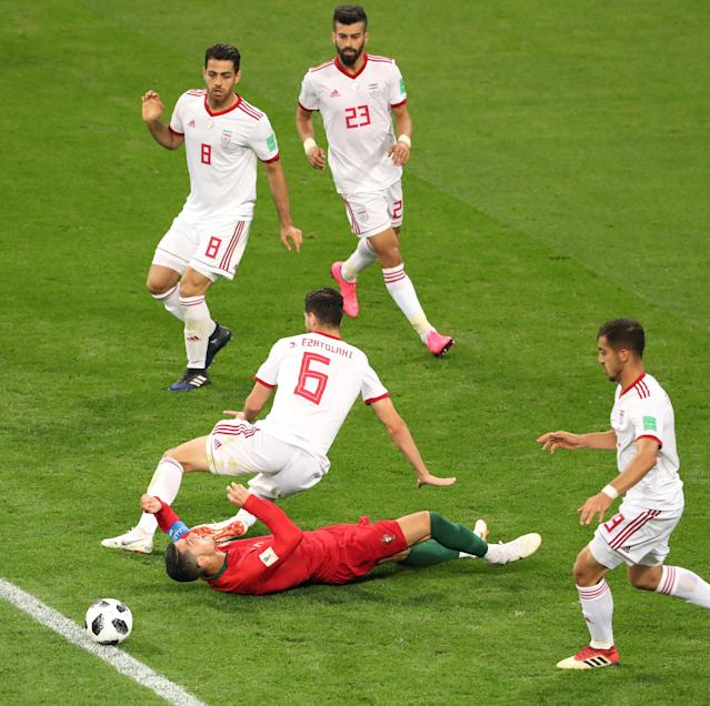 Soccer Football - World Cup - Group B - Iran vs Portugal - Mordovia Arena, Saransk, Russia - June 25, 2018 Portugal's Cristiano Ronaldo goes down under the challenge of Iran's Saeid Ezatolahi prompting referee Enrique Caceres to award Portugal a penalty after a VAR referral REUTERS/Lucy Nicholson
