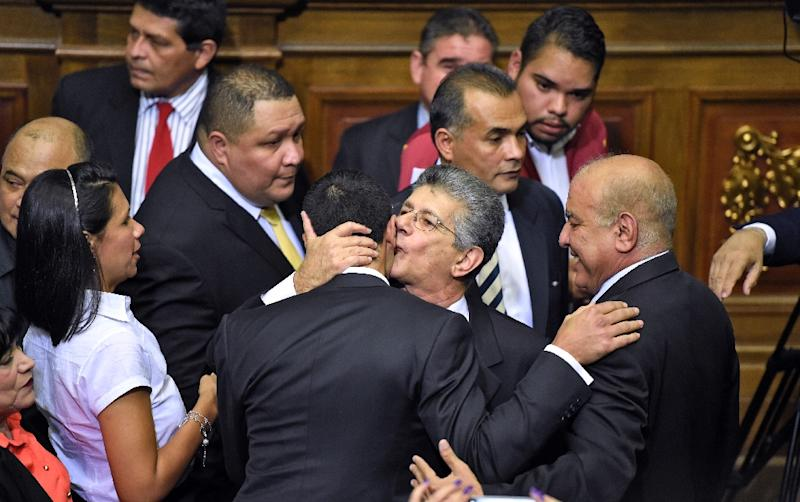 The new president of the Venezuelan parliament, Henry Ramos Allup (C) is greeted by other opposition lawmakers at the parliament in Caracas, on January 5, 2016 (AFP Photo/Juan Barreto)