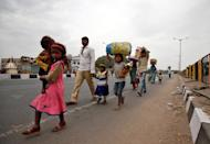 Migrant workers walk with their children as they look out for transport to return to their villages, after India ordered a 21-day nationwide lockdown to limit the spreading of coronavirus disease (COVID-19), in Ahmedabad, India, March 25, 2020. REUTERS/Amit Dave