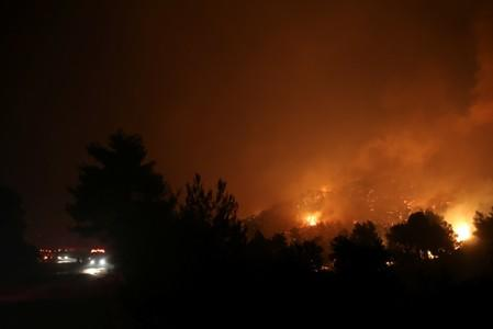 Flames rise next to firefighting vehicles as a wildfire burns near the village of Makrimalli on the island of Evia