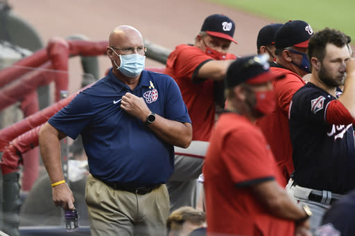 Washington Nationals general manager Mike Rizzo, left, looks on from the dugout as a baseball game against the Atlanta Braves gets underway, Saturday, Sept. 5, 2020, in Atlanta. Rizzo, who also holds the title of president of baseball operations, built the team that won the 2019 World Series championship and just finalized a multiyear contract extension with the team. (AP Photo/John Amis)