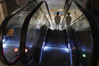A medical members staff uses the escalator at Bichat Hospital, AP-HP, in Paris, Wednesday, Dec. 2, 2020. One of the biggest hospitals in Paris, Bichat Hospital, this month reopened all 22 of its operating rooms. It is once again performing surgeries that were stopped during virus surges that pushed France's death toll past 55,000. (AP Photo/Francois Mori)