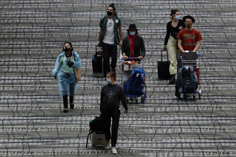 Travellers wearing protective masks seen walking along the transit area of Changi International Airport terminal 15 December. (PHOTO: Getty Images)