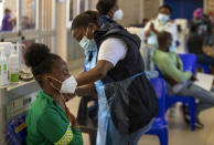Khensani Chauke, a professional paramedic, receives a dose of Johnson & Johnson COVID-19 vaccine from a health staff member during a vaccination day for healthcare workers at a vaccination centre at Chris Hani Baragwanath Academic Hospital in Johannesburg, South Africa, Friday, March 26, 2021. (AP Photo/Themba Hadebe)