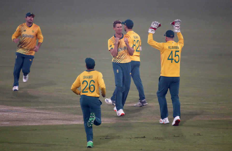 South Africa's Dwaine Pretorius, center, celebrates with teammates after taking the wicket of Pakistan's Babar Azam dismissal during the 2nd Twenty20 cricket match between Pakistan and South Africa at the Gaddafi Stadium, in Lahore, Pakistan, Saturday, Feb. 13, 2021. (AP Photo/K.M. Chaudary)