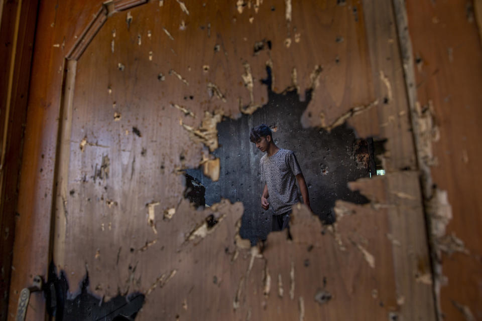 A Kashmiri man inspecting a house where suspected rebels had taken refuge is seen through a hole created by a mortar shell fired by government forces during a gunfight, in Srinagar, Indian-controlled Kashmir, on Friday, July 16, 2021. Two suspected rebels were killed in a gunfight in in the disputed region's main city on Friday, officials said, as violence increased in recent weeks. (AP Photo/ Dar Yasin)