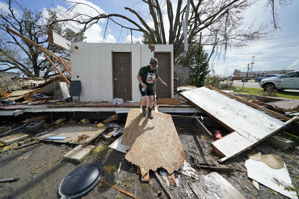 Nicole Beard searches for belongings in the debris of what was the trailer home she lived in, in Hackberry, La., in the aftermath of Hurricane Laura, Saturday, Aug. 29, 2020. (AP Photo/Gerald Herbert)