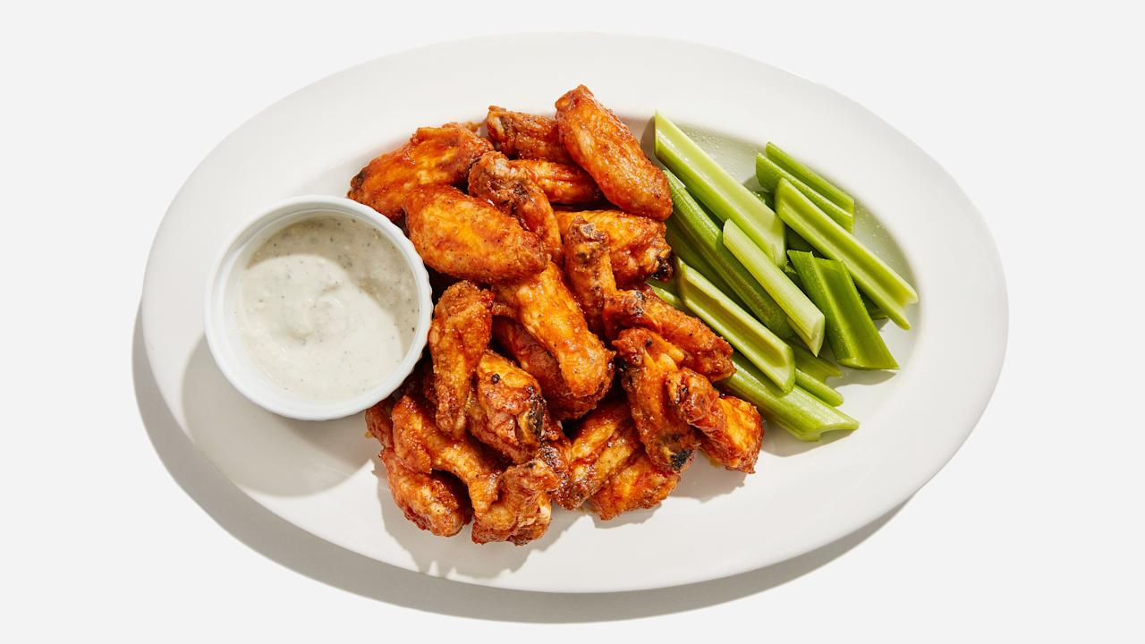 """Want crispy-spicy chicken wings without having to deep-fry at home? We got you. A few tricks guarantee oven-baked wings that are every bit as irresistible as the ones you get at the bar. First, adding baking soda to the dry rub does something...science-y to the chicken skin that facilitates extra crispiness. And starting the wings at a low temperature before blasting them with high heat helps to render out some of the fat from the skin as well, which gets them brown faster. Want to double or triple this recipe for a crowd? You can bake them all at the lower temperature before guests arrive, pull them out, and crisp them up one batch at a time so everyone gets piping hot wings. <a href=""""https://www.bonappetit.com/recipe/basically-buffalo-wings?mbid=synd_yahoo_rss"""">See recipe.</a>"""